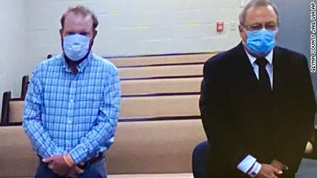 Travis McMichael, left, and Greg McMichael listen to a preliminary hearing via video feed Thursday.