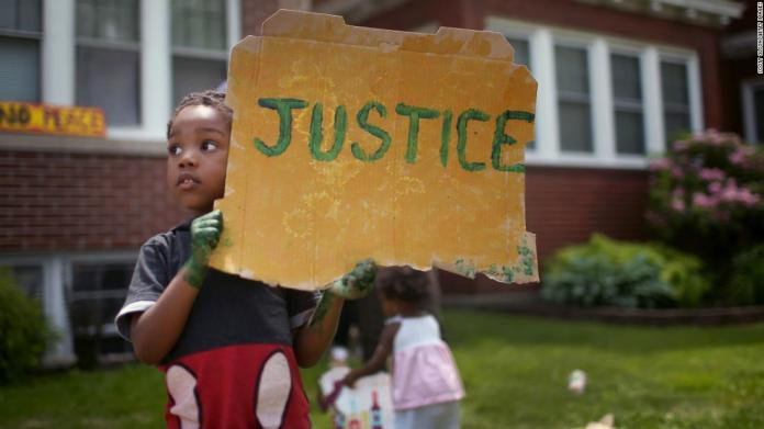 Xavier Brown shows his support as demonstrators march past his home in St. Paul, Minnesota, on June 6.
