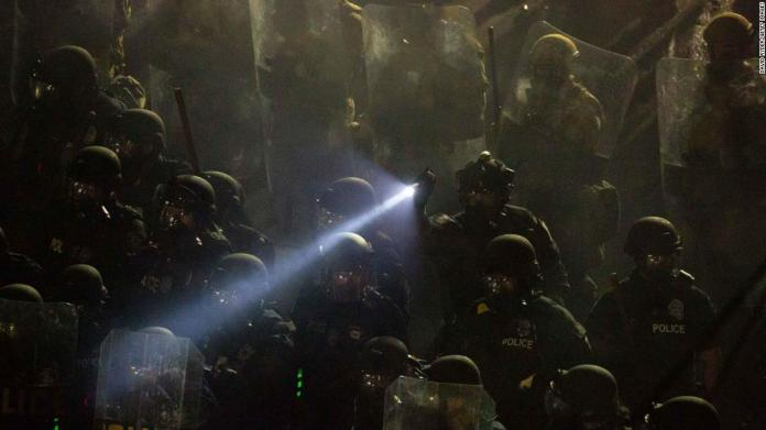 Seattle Police and Washington National Guard personnel retake control of an intersection as demonstrators clash with law enforcement near the Seattle Police Department's East Precinct shortly after midnight on June 8.