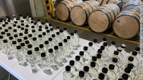 Ряды дезинфицирующих средств для рук, производимых при закрытии на заводе в Бруклине, который обычно производит виски в Нью-Йорке