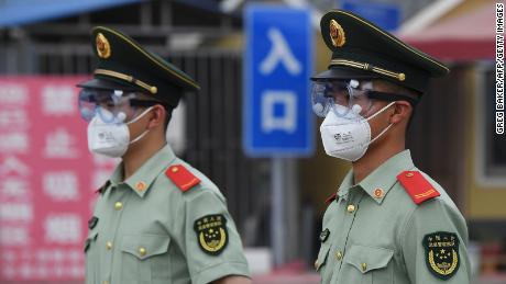 Paramilitary police officers wear face masks and goggles as they stand guard at an entrance to the closed Xinfadi market in Beijing on June 13.
