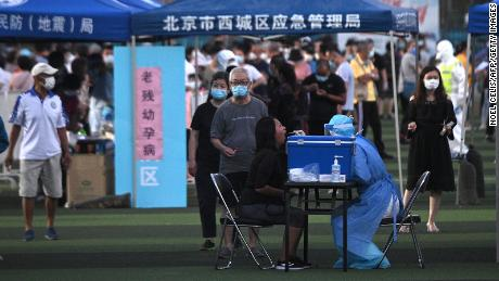 A health worker wearing a protective suit takes a swab test from a woman at a testing center set up for people who visited or live near the Xinfadi market in Beijing.