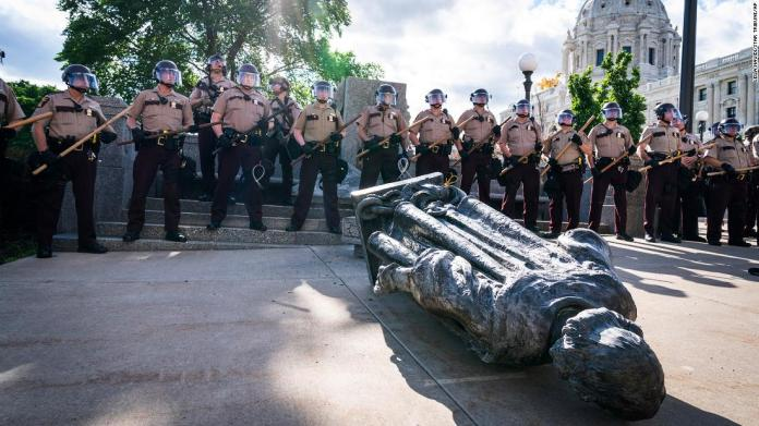 "Minnesota state troopers surround a statue of Christopher Columbus after activists pulled it down in front of the Capitol in St. Paul on Wednesday, June 10. <a href=""https://www.cnn.com/2020/06/10/us/christopher-columbus-statues-down-trnd/index.html"" target=""_blank"">Columbus has long been a contentious figure in history</a> for his treatment of the Indigenous communities he encountered and for his role in the violent colonization at their expense."