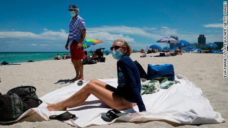 Диана, медсестра из Хьюстона, штат Техас, загорает на пляже рядом со своим мужем, оба в масках, в Майами-Бич, штат Флорида.