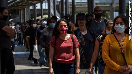 Пассажиры выстраиваются в линию, чтобы пересечь в Соединенные Штаты в порту пересечения Сан-Исидро в Тихуане 16 июня 2020 года.