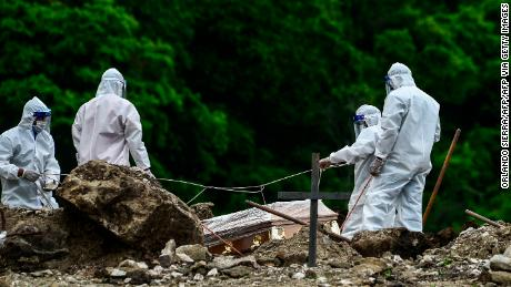 Men in protective gear bury a coronavirus victim in a cemetery 14 km north of the Honduran capital Tegucigalpa on June 21, 2020.