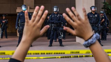 A demonstrator holds her hands up while she kneels in front of police on June 1, 2020 in Anaheim, California, during a peaceful protest over the death of George Floyd.