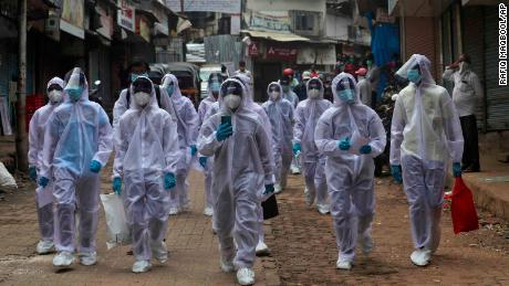 Health workers arrive at a medical camp in a slum area of Mumbai, India, June 28,