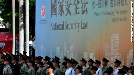 Attendees from various forces stand next to a banner supporting the new national security law during a flag-raising ceremony to mark China's National Day celebrations early morning in Hong Kong on July 1, 2020.
