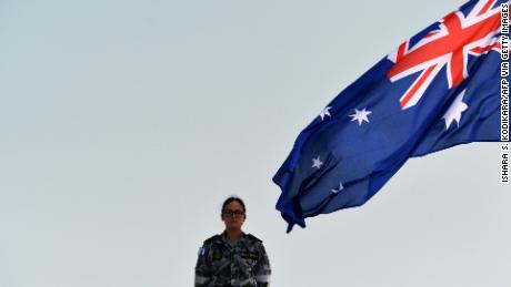 A Royal Australian Navy personnel stands next to the Australia's national flag as she takes part in training excercise in the Sri Lankan capital Colombo on March 26, 2019.
