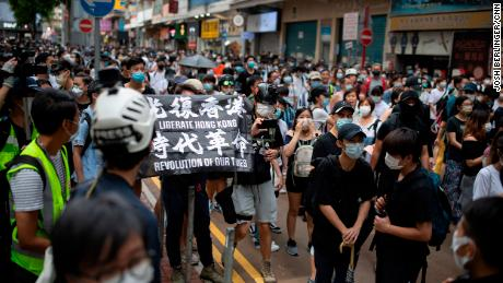 """A protester is seen carrying a flag that says """"Liberate Hong Kong, revolution of our times,"""" an act that could now be considered a crime under the city's new national security law."""