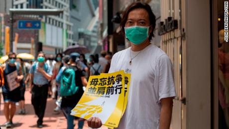 District Councilman and attorney Lawrence Lau holds a sign in Hong Kong's Causeway Bay district, shortly before police began cleaning up the area on Wednesday.
