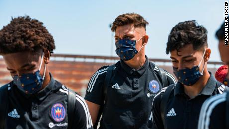 Members of Chicago Fire FC don masks on the way to training.