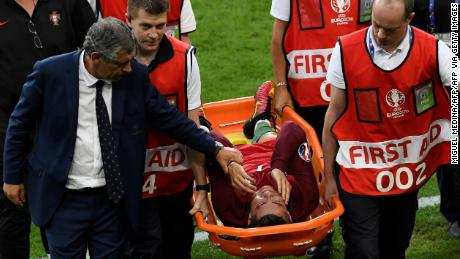 Cristiano Ronaldo is comforted by Portugal coach Fernando Santos as leaves the field on a stretcher during the Euro 2016 final.