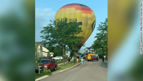 A hot air balloon made an emergency landing in an Illinois neighborhood after a passenger fainted