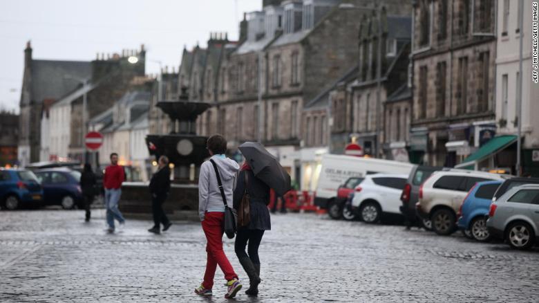 La gente cammina oltre una fontana a St Andrews, in Scozia.