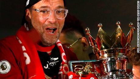Jurgen Klopp poses with the Premier League trophy.