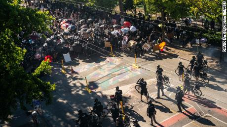 Police push demonstrators back atop a Black Lives Matter street mural during protests in Seattle on July 25, 2020, in Seattle, Washington.