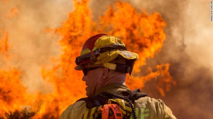 A firefighter watches the Apple Fire in Cherry Valley, California, on Saturday.