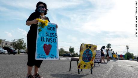 Anna Perez, 53, holds a sign during a drive-through vigil in El Paso, Texas, honoring the 23 victims of the Walmart shooting on Saturday.