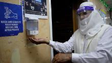 A volunteer uses hand sanitizer as he enters Minhaj-ul-Quran Mosque in London on July 31.