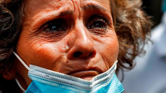 A woman, whose son was said to be missing after the explosion, waits outside Beirut's port to receive information from rescue teams.