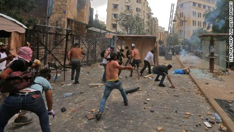 Protesters hurl rocks towards security forces during clashes in downtown Beirut, Lebanon, on Saturday.