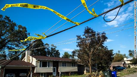 Caution tape is wrapped around a low downed power line that stretches over a roadway, Thursday, Aug. 13, 2020, after a derecho in Cedar Rapids, Iowa.