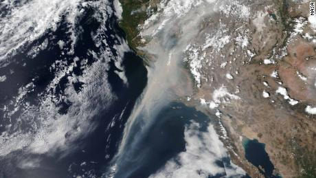 Smoke from the California wildfires stretches some 600 miles off the coast in a NASA satellite image Wednesday.