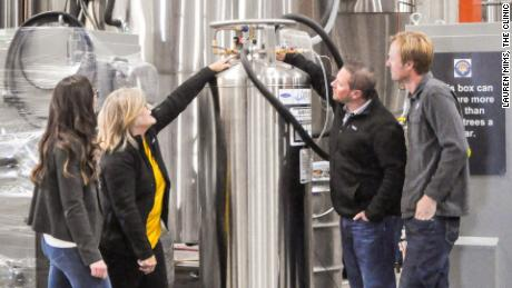 Kaitlin Urso (Colorado Department of Public Health and Environment), Amy George (Earthly Labs), Brian Cusworth (The Clinic) and Charlie Berger (Denver Beer) checking the valves for Denver Beer's CO2 tank and Earthly Labs' CO2 recovery equipment that will later be used in The Clinic's cannabis plants.