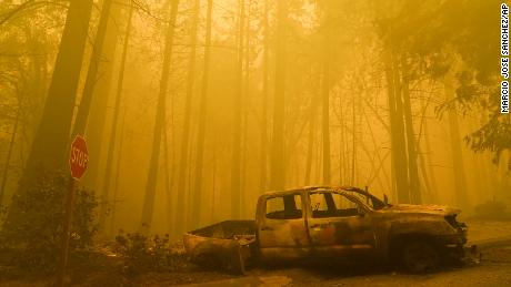 A burned out vehicle is left in front of a fire- ravaged residence as smoke fills the sky on Saturday, August 22, in Boulder Creek, California.