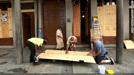 Workers mount windows in the French Quarter in anticipation of Hurricane Marco and Tropical Storm Laura.