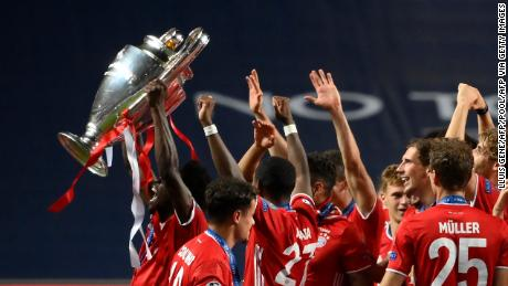 Alphonso Davies holds the Champions League the trophy aloft after beating PSG.