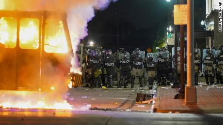 Police stand near a garbage truck ablaze during protests Monday in Kenosha
