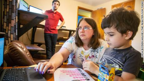 Kara Vaughn helps her son Simon, a kindergartner, get ready for class on the zoom at their home in Urundale, Iowa, on July 30, 2020.
