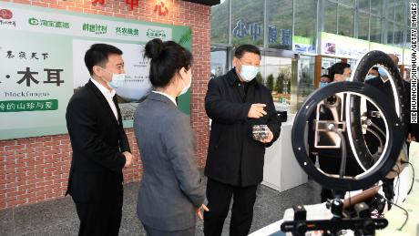 Chinese President Xi Jinping talking to a live-streaming host during the set-up of a live shopping session to market local produce in Jinmi, Zhashui county, northwest China's Shaanxi province in April.