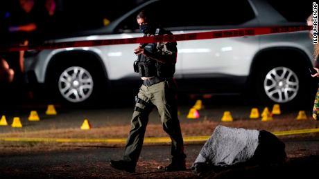 Police walk past evidence markers at the scene where Michael Reinoehl was killed as investigators moved in to arrest him in Lacey, Washington.