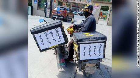 """Some food delivery workers in Inner Mongolia have stuck signs reading """"save our mother tongue"""" on their bikes."""