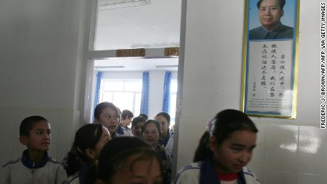 Students walk past a portrait of China's late Chairman Mao Zedong at a bilingual middle school for Uyghur and Han Chinese students in Hotan, Xinjiang in 2006.