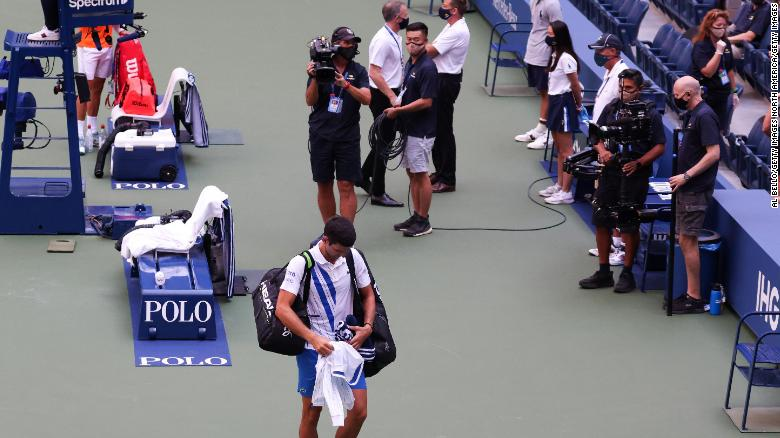 Novak Djokovic walks off court at the US Open after being defaulted.