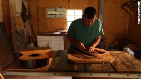 Earl Moore works on a guitar he made from scratch. He credits wood working, in large part, for eight years of sobriety.