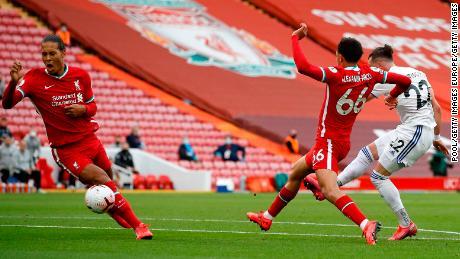 Jack Harrison of Leeds United scores his team's opening goal at Anfield as he shoots home past Liverpool defenders Trent Alexander-Arnold and Virgil Van Dijk.