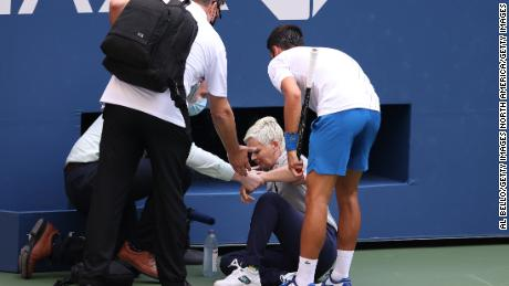 Djokovic tends to the judge after striking her with a ball.