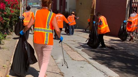 Clad in orange vests, homeless people working with Wheels of Change approach their assigned area to clean up. Wheels of Change pays 20 people each day to pick up litter around San Diego, in an effort to lift them out of homelessness.