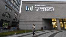 A woman walks past the headquarters of ByteDance, the Chinese parent company of video app TikTok.