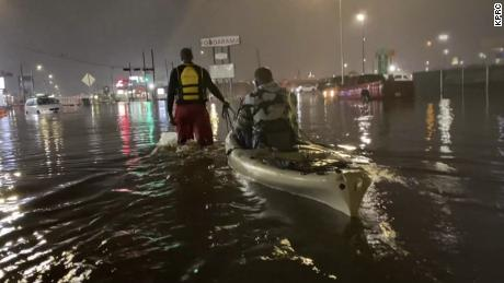 A man is pulled to safety in a kayak after being rescued from his vehicle that had stalled in floodwaters caused by Tropical Storm Beta in Houston on Sept. 21, 2020.