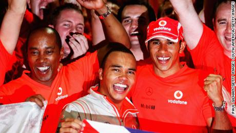 Lewis Hamilton celebrates his first world title in 2008 with father Anthony Hamilton and his brother Nicolas Hamilton.