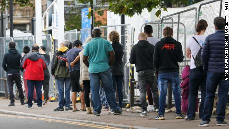 Visitors stand in line at a coronavirus walk-in testing center in Edmonton, London, on Wednesday.