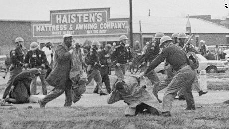In this March 1965 photo, a state trooper swings a billy club at John Lewis, right foreground, chairman of the Student Nonviolent Coordinating Committee, to break up a civil rights voting march in Selma, Alabama. Lewis sustained a fractured skull.