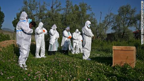 Relatives wearing personal protective equipment offer funeral prayers for a woman who died of coronavirus, during her burial in a cemetery in Srinagar on May 21, 2020.